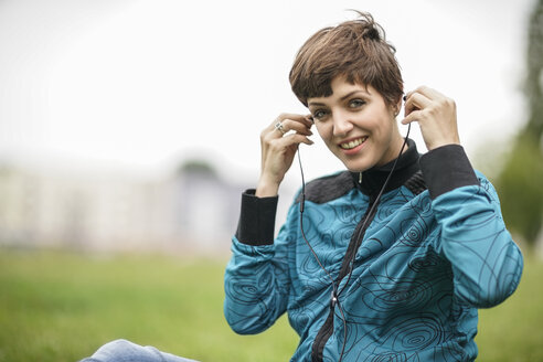 Portrait of smiling young woman with earphones sitting on a meadow - TAMF00754