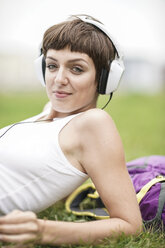 Portrait of smiling young woman lying on a meadow listening music with  headphones - TAMF00757
