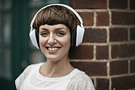 Portrait of smiling young woman listening music with white headphones - TAMF00766