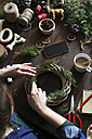 Woman decorating Advent wreath on work table, partial view - RTBF00477
