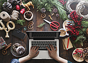 Woman working with laptop at her desk covered with utensils for creating Advent wreaths, partial view - RTBF00480