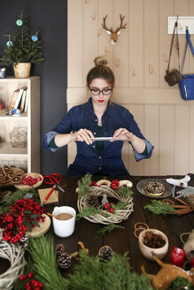 Woman taking picture of self-made Advent wreath with smartphone - RTBF00489