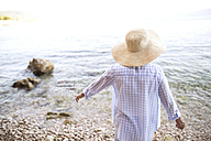 Back view of woman wearing straw hat standing at seafront - HAPF01035