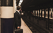 Young businessman waiting at metro station platform - UUF08997