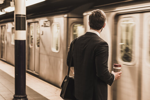Young businessman waiting at metro station platform, holding disposable cup - UUF09000