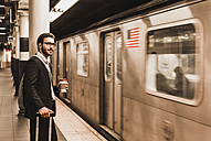 Young businessman waiting at metro station platform, holding disposable cup - UUF09003
