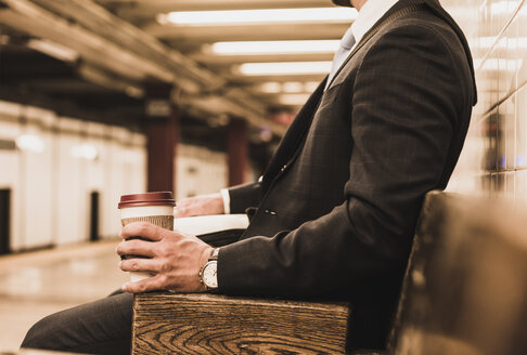 Young businessman waiting at metro station platform, holding disposable cup - UUF09006