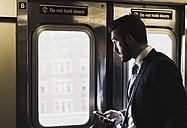 Young businessman taking metro, using smart phone - UUF09009
