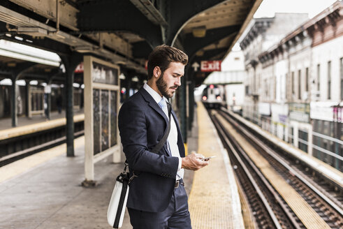 Young businessman waiting at metro station platform, using smart phone - UUF09021