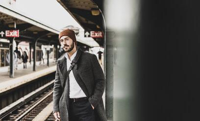 Young man waiting at metro station platform - UUF09024