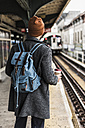 Young man waiting at metro station platform, holding disposable cup - UUF09027