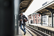 Young man waiting for metro at train station platform, using smart phone - UUF09030