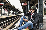 Young man waiting for metro at train station platform, using smart phone - UUF09033