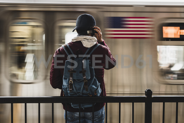 Young man waiting for metro at train station platform, wearing headphones - UUF09048
