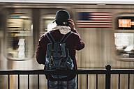 Young man waiting for metro at train station platform, wearing headphones - UUF09048