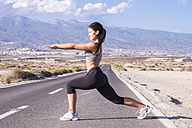 Young woman doing stretching exercises on an empty road - SIPF01025