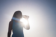 Young sportive woman drinking water - SIPF01034