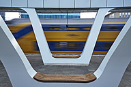 Netherlands, Arnheim, benches at platform of central station with train passing by in the background - BSC00547