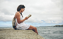 Smiling woman with backpack sitting on pier reading a book - DAPF00459