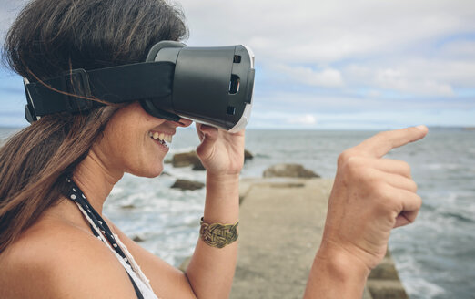 Smiling woman using Virtual Reality Glasses outdoors - DAPF00468
