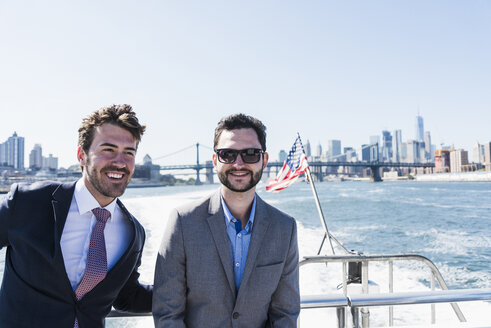 USA, New York City, two smiling businessmen on ferry on East River - UUF09051