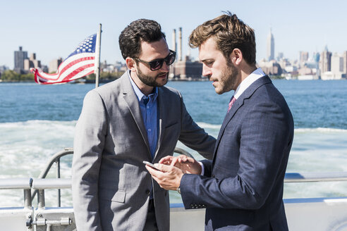 USA, New York City, two businessmen with cell phone on ferry on East River - UUF09060