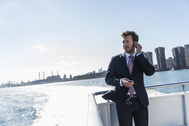 USA, New York City, businessman on ferry on East River with cell phone and earphones - UUF09063