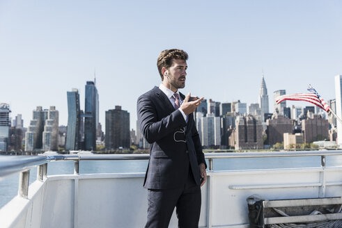 USA, New York City, businessman telephoning on ferry on East River - UUF09066