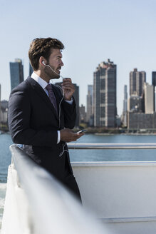 USA, New York City, businessman telephoning on ferry on East River - UUF09069