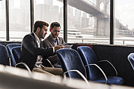 Two businessmen with document talking on passenger deck of a ferry - UUF09084