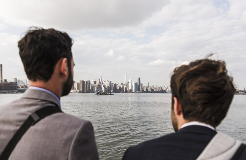 USA, New York City, back view of two businessmen at East River - UUF09102