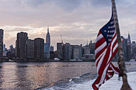 USA, New York City, US flag on ferry on East River with skyline of Manhattan in background - UUF09117