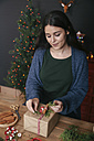 Young woman decorating Christmas present - RTBF00498
