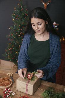 Young woman decorating Christmas present - RTBF00498