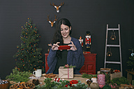 Smiling young woman photographing decorated Christmas gift with smartphone - RTBF00501