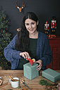 Portrait of smiling young woman wrapping Christmas present - RTBF00507