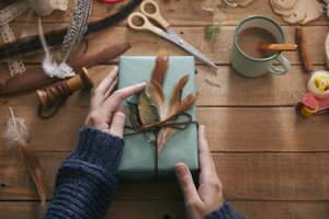 Woman decorating Christmas present with leaf and feathers, close-up - RTBF00510