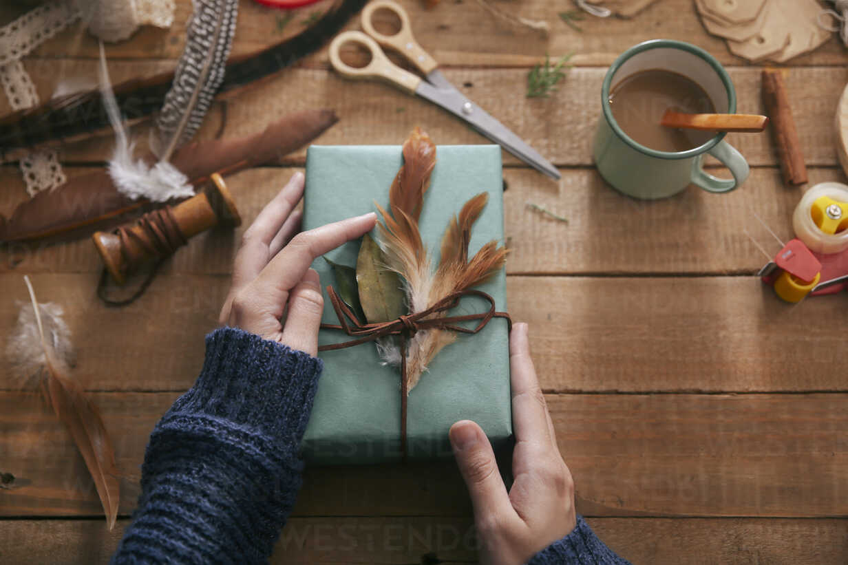 Woman decorating Christmas present with leaf and feathers, close-up - RTBF00510 - Retales Botijero/Westend61