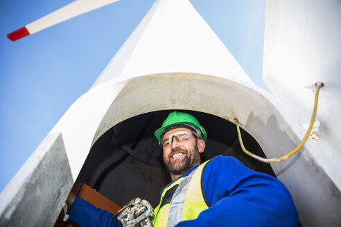 Engineer inspecting wind turbine, using wrench - ZEF11513