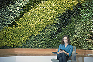Businesswoman using smart phone in front of green plant wall - WESTF21883