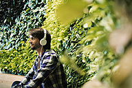 Young man sitting in front of green plant wall, wearing head phones - WESTF21907