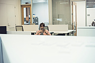 Man working in office, looking at smart phone - WESTF21919