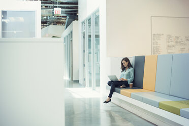 Young businesswoman sitting on bench, using laptop - WESTF21922