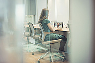 Businesswoman sitting in office, using laptop for video conference - WESTF21967