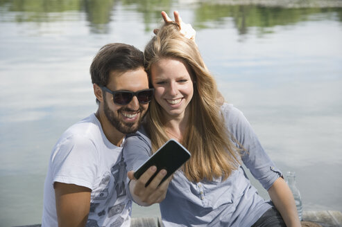 Playful young couple at a lake taking a selfie - CRF02762