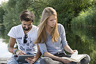 Young couple sitting on jetty at a lake with book and tablet - CRF02765