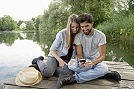 Smiling young couple sitting on jetty at a lake with cell phone - CRF02771
