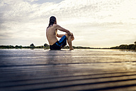 Man sitting on jetty at the water - BMAF00282