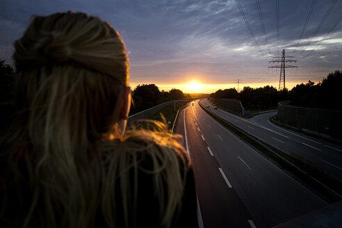 Woman looking at sunset behind motorway - BMAF00285