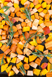 Sliced pumpkin, carrots and sweet potatoes with twigs of rosemary on baking tray - SARF03053